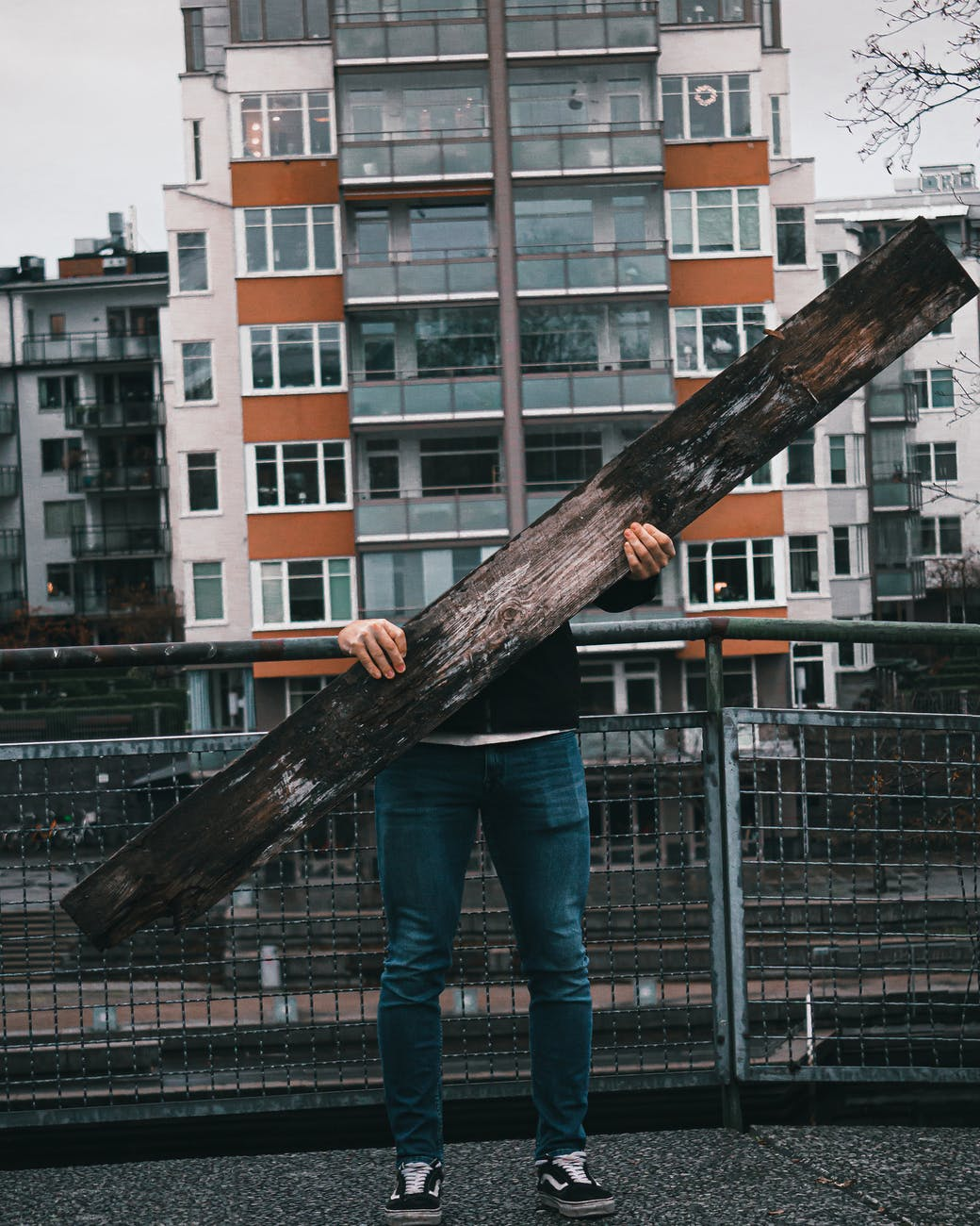 person in blue denim jeans standing holding brown wooden log